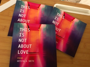 Three copies of This is Not About Love Poetry book on a tan colored lap desk.